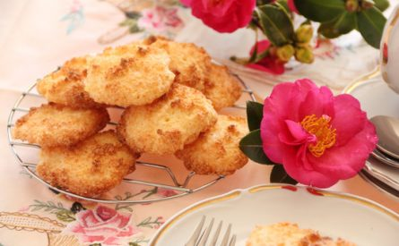 Fresh baked coconut macaroons ready to serve with a camellia.